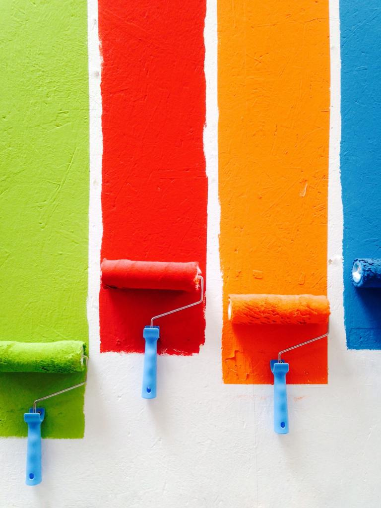 Four painting rollers painting green, red , orange and blue on a wall