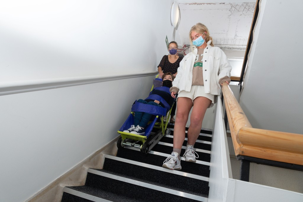 Woman pushing petite woman in evacuation chair down a stairwell. Disabled woman is looking a young person walk passed her