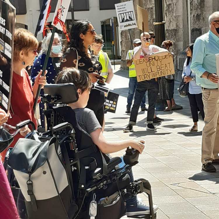 A photograph taken from a protest. About 10 people can be seen, carrying placards and listening to a speaker. One person is a powered wheelchair user.