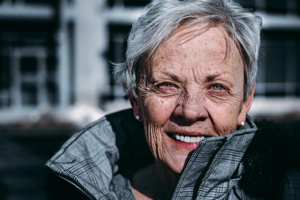 Older white woman with short grey hair and a trenchcoat is smiling