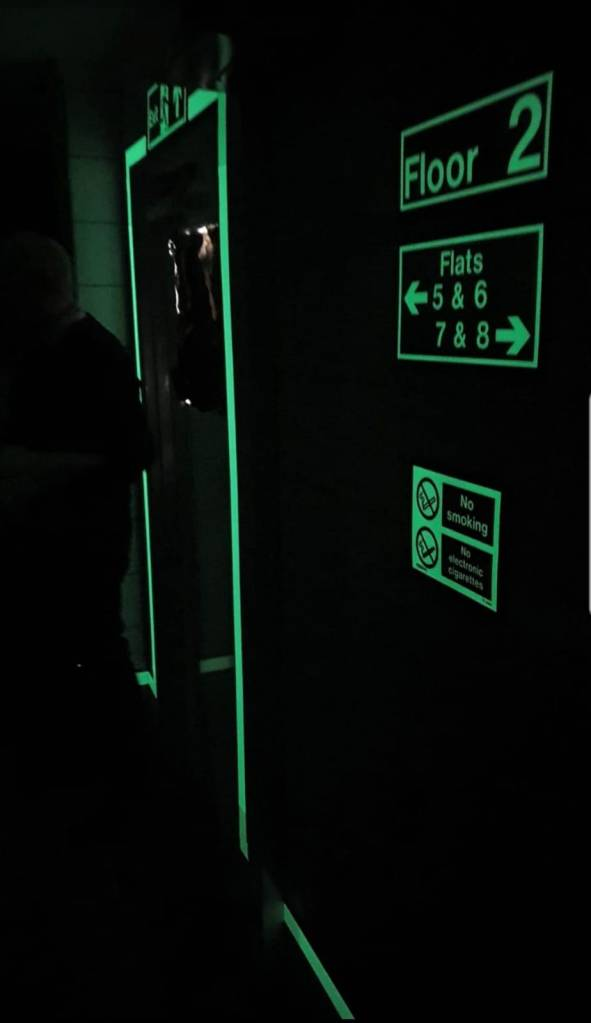 A stairwell in darkness, with a green glow-in-the-dark effect system that highlights door edges and signage
